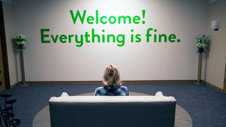 """eleanor est assise devant un mur disant """"Bienvenue ! Tout va bien"""""""