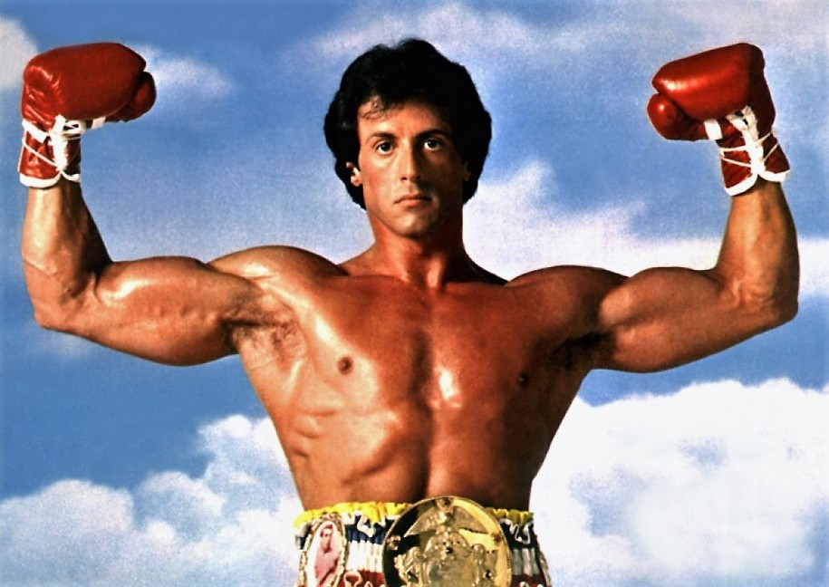 Sylvester Stallone de face montrant ses muscles
